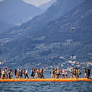 LAKE ISEO, ITALY - JULY 1,  2016: people walking on the Floating Piers,  site specific landscape artwork by Christo and Jeanne Claude
