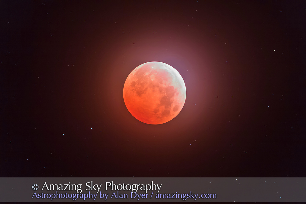 The total eclipse of the Moon, October 8, 2014, the Hunter&rsquo;s Moon, as seen and shot from Writing-on-Stone Provincial Park, Alberta under mostly clear though slightly hazy skies, thus the glow around the Moon. The planet Uranus is the brightest dot left of the Moon at 8 o&rsquo;clock position. Both the Moon and Uranus were at opposition. This was the second in a &ldquo;tetrad&rdquo; series of 4 total lunar eclipses in a row at six-month intervals in 2014 and 2015.<br /> <br /> I shot thus just after mid-totality though with the northern limb of the Moon still bright in this single 15-second exposure at ISO 400 with the Canon 60Da, and with the Officina Stellaire 80mm apo refractor at f/6. It was mounted on the Sky-Watcher HEQ5 mount tracking at the lunar rate. I chased into clear skies to see and shoot this eclipse.