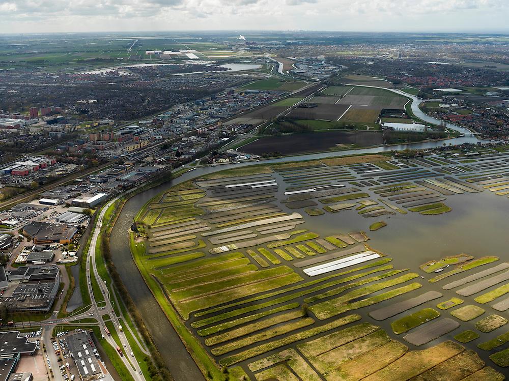 Nederland, Noord-Holland, Gemeente Langedijk, 16-04-2012; het Kanaal Alkmaar - Kolhorn scheidt bedrijventerrein Zandhorst in Heerhugowaard (links) van landschapsreservaat Oosterdel. Dit gebied vormt een restant van het 'duizend eilandenrijk', voormalige veengronden ontstaan door ontwatering en afgraven van veen en in gebruik voor tuinbouw. Onderdeel van de Provinciale Ecologische Hoofdstructuur (EHS). Bebouwing Alkmaar (rechts) en Heerhugowaard (links) in de achtergrond, polder De Schermer aan de horizon..Landscape reserve Oosterdel (NW Netherlands) . This area is a remnant of thousand islands, former peatlands caused by drainage and excavation of peat and is used horticulturally. Part of the Provincial  Ecological Structure  (EHS). .luchtfoto (toeslag), aerial photo (additional fee required);.copyright foto/photo Siebe Swart