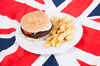 Close-up of hamburger and chips over British flag