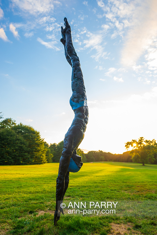 "Old Westbury, New York, U.S., September 1, 2019. ""Athlete III - Deep Plunge"" is one of 33 outdoor sculptures by Jerzy Kedziora (Jotka), b. 1947 in Poland,, and his Balance in Nature art is on view at historic Old Westbury Gardens in Long Island, until October 20, 2019. Seen at dusk, the life-size, bronze resin balancing sculpture, dressed in blue swimwear, appears about to dive into the lawn."