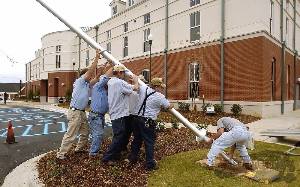 Photo by Gary Cosby Jr.  Workers Mike Nave, Tommy Raby, Tommy Hemphill, Harold Taylor Fred Wels and David Seibert raise a flag pole at the new Limestone County Courthouse Annex.