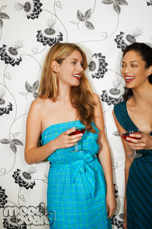 Two women Drinking Martinis by floral print wall