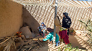 Lady prepares madfouna - the Berber pizza - in a mud oven at an earthen home in Hassilabied village, Southern Morocco, 2017-12-21. <br />