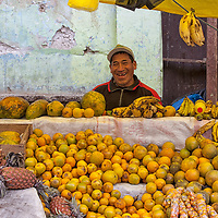 A man selling oranges at a market in Tarma.