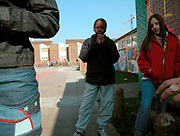 A group of teenage girls hanging out in a paved area outside a housing estate London 2000