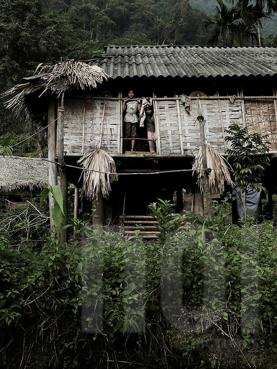 Two young girls inside an old ethnic house are observing outside through a big window. The stilt house is made of wood and palm tree leaves. Pu Luong area, Hoa Binh, Vietnam, Asia.
