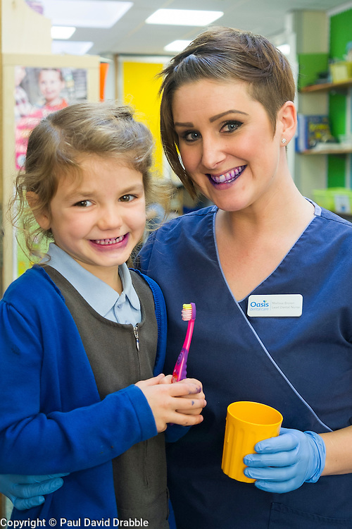 Oasis Lead Dental Nurse Mel Brown with Margot after using the disclosure tablets to reveal plaque in the mouth during an oral hygiene session at  Hunloke Park Primary School Wingerworth Chesterfield on Tuesday<br /> 20 October 2015<br />  Image © Paul David Drabble <br />  www.pau ldaviddrabble.co.uk