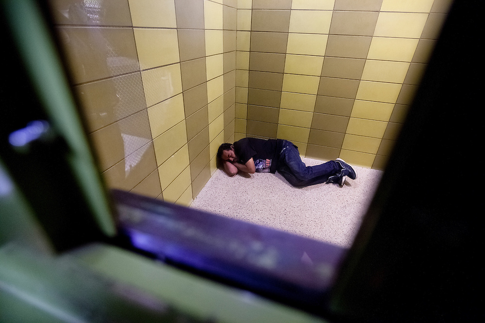 A man who was arrested for driving under the influence sleeps on the floor of the city jail. Dec. 6, 2011. Oxnard, Calif. (Photo by Gabriel Romero ©2011)