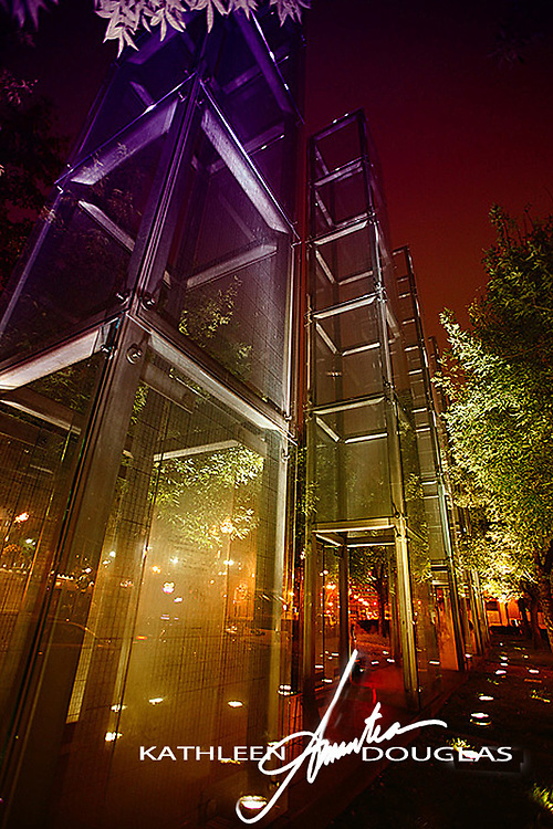 New England Holocaust Memorial Boston at night. The memorial features six glass towers, 54 ft high ,  lit internallyand set on a black granite path.  Each structure is  carries the name of  principal  a Nazi death camp  built over dark chambers, that smoke from charred embers in the bottom.  Six million numbers are etched into the glass recalling the six million jews who died in Nazi War Camps. Excerpt from the NEHM website.   See more at www.nehm.org