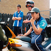 Group of lads standing around with some mopeds looking bored