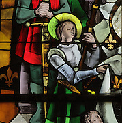 Stained glass window of St Joan of Arc by Max Ingrand, 1957, in the Gothic choir of the Chapelle Saint-Calais, built 1498-1508, in the courtyard on the Louis XII wing of the Chateau Royal de Blois, built 13th - 17th century in Blois in the Loire Valley, Loir-et-Cher, Centre, France. The chapel was consecrated in 1508 by Antoine Dufour, bishop of Marseille. The choir with its vaulted ceiling and stained glass by Max Ingrand, 1957, remains, although the nave was destroyed by Mansart during works under Gaston d'OrlÈans.The chateau has 564 rooms and 75 staircases and is listed as a historic monument and UNESCO World Heritage Site. Picture by Manuel Cohen