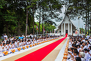19 JULY 2014 - KHLONG LUANG, PATHUM THANI, THAILAND: Lay people wait to present newly ordained monks with their robes at Wat Phra Dhammakaya. Seventy-seven men from 18 countries were ordained as Buddhist monks and novices at Wat Phra Dhammakaya, a Buddhist temple  north of Bangkok, Saturday. It is the center of the Dhammakaya Movement, a Buddhist sect founded in the 1970s and led by Phra Dhammachayo (Phrathepyanmahamuni). It is the largest temple in Thailand. The Dhammakaya sect has an active outreach program that attracts visitors from around the world.    PHOTO BY JACK KURTZ