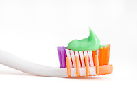Close up of a toothbrush over white background with toothpaste.