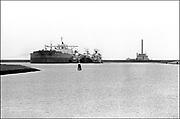 Nederland, Groningen, 15-10-1985<br /> De Eemshaven was ontworpen voor grootschalige activiteiten in de olieraffinage en basischemie. De oliecrisis van 1973 was echter een spaak in het wiel, waardoor er geen olie- noch chemische industrie van de grond kwam. De enige bron van inkomsten vormden grote schepen, die in de haven tijdelijk gestald werden en waarvoor het havenschap geld ontving . Een van de topattracties was de olietanker Aiko Maru met 430.000 ton draagvermogen. Dat schip arriveerde op 22 april 1983, en was de oorzaak van de langste file ooit in de Provincie Groningen: 22 kilometer, van Delfzijl naar de Eemshaven.