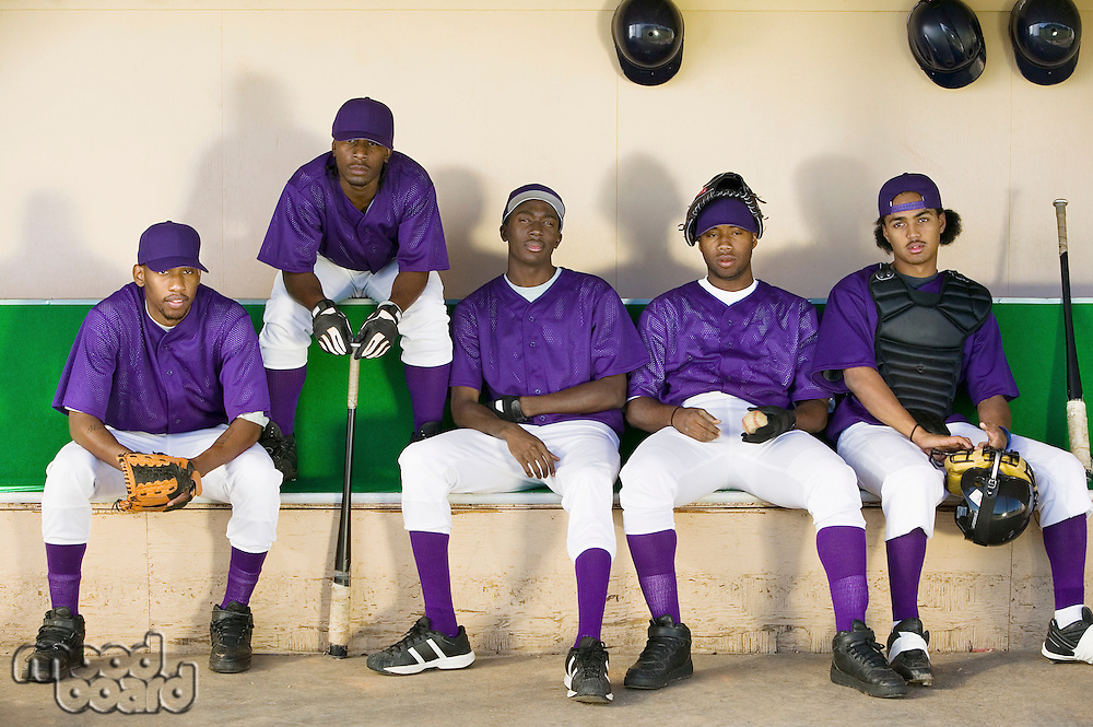 Baseball team sitting in dugout (portrait)