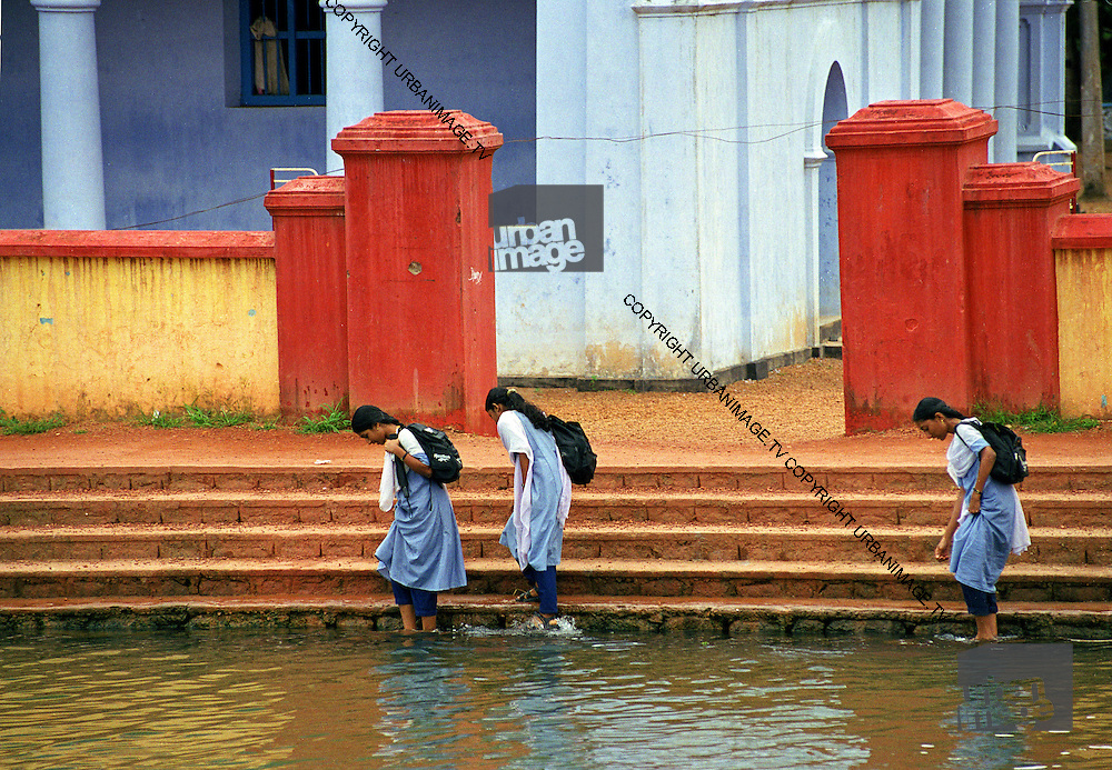 School girls in blue washing feet at school on Backwater - Kerala India