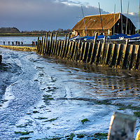 The harbour at Bosham in West Sussex while the tide is out during winter at sunset