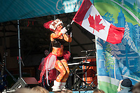 The musical band, Wassabi Collective, plays to a crowd in Whistler village on a sunny warm afternoon during the 2010 Olympic Winter Games in Whistler, BC Canada. The 5-piece band from Nelson, BC included additional body-painted hula hoop dancers, beach balls and extra fun.