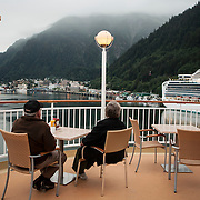 Two passengers on the Norwegian Pearl watch it dock near the Diamond Princess, a cruise ship owned and operated by Princess Cruises docked at the port in Juneau, Alaska<br /> Photography by Jose More