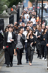 © Licensed to London News Pictures. 29/06/2017. London, UK. Mourners walk to the church as the coffin of Grenfell Tower fire victim Tony Disson is carried in a horse drawn hearse to Our Lady of the Holy Souls church for a funeral service in Kensal, West London. Mr Disson is one of only a handful of the 80 victims to have been identified and named so far. Photo credit: Peter Macdiarmid/LNP