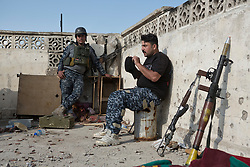 Licensed to London News Pictures. 02/04/2017. Mosul, Iraq. Two Iraqi Federal Police officers relax on a West Mosul rooftop after firing at nearby Islamic State militants.<br /> <br /> Iraqi forces continue to fight house to house as they push further into West Mosul. Iraqi forces are now advancing on the city's old districts where Islamic State fighters still hold out. Photo credit: Matt Cetti-Roberts/LNP