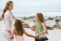 Mother playing with two daughters (7-9 10-12) on beach