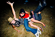 Three girls fallen on the floor wearing one pair of Knickers. Global Gathering festival, Long Marston Airfield, Stoke on Trent, UK. 28/29 July 2006