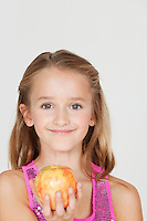 Portrait of young girl holding an apple against gray background