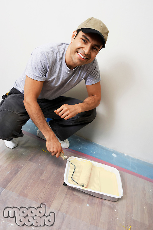 Man Loading Roller with Paint