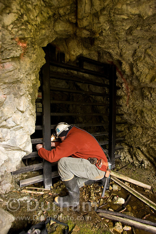 Geologist and mining engineer Greg Graham unlocks a bat gate at the entrance to the abandoned Gold Stake gold mine. The gate is designed to allow bats to fly in and out of the mine interior while keeping human visitors and other large animals excluded. Greg is going to inspect the mine in preparation for a bat survey by biologists. Coleville National Forest, Washington.