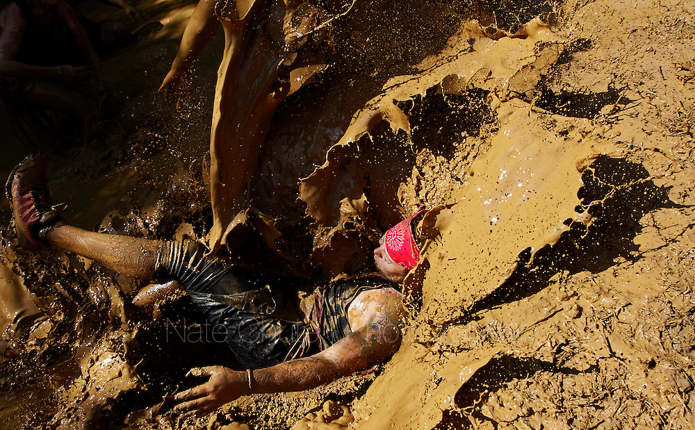 A participant falls into muddy water after getting over a muddy mound during the Warrior Dash obstacle race in Crawfordsville, Indiana August 17, 2013.  Competitors run through mud, climb walls and crawl under barbed wire during the 3.2 mile (5.2 km) race.  REUTERS/Nate Chute  (UNITED STATES)