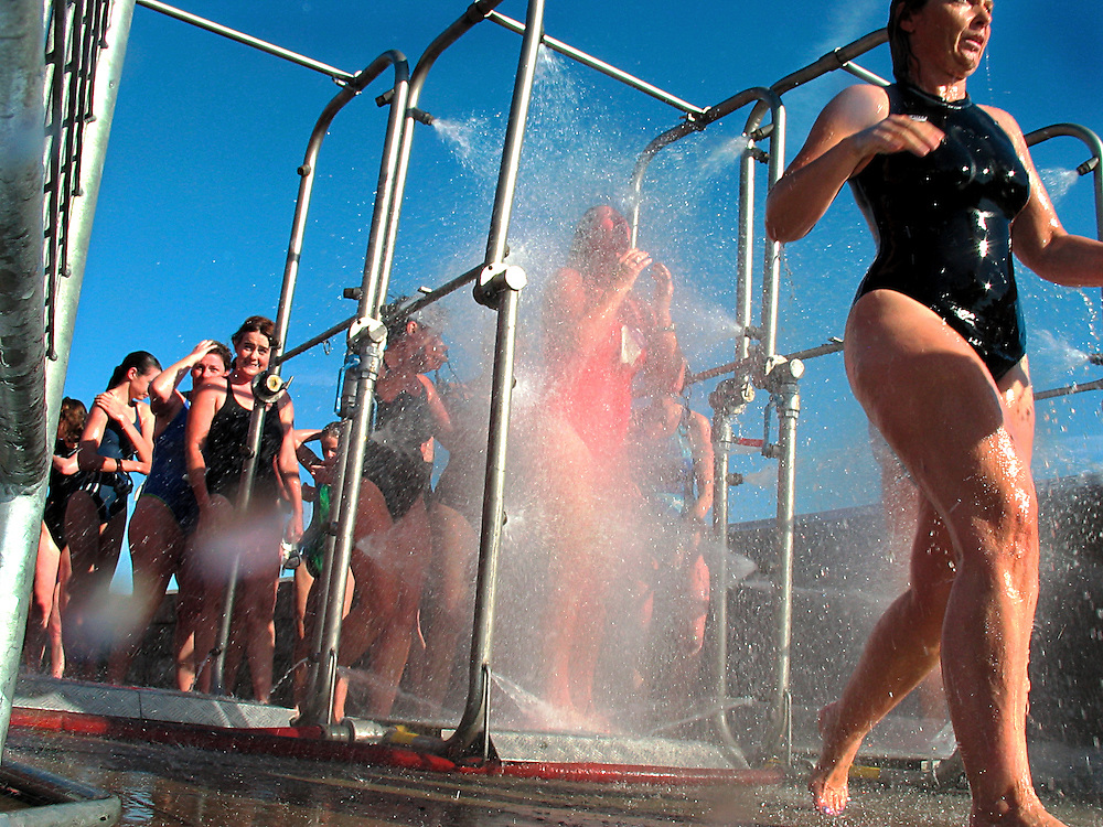 Swimmers shower and wash with disinfectant after completing the 2004 Liffey Swim. Dublin Ireland, September 2004.