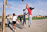 Pine Ridge Sioux Indian Reservation, Oglala, South Dakota, Oglala Sioux (Lakota) Indian boys play basketball, government housing complex
