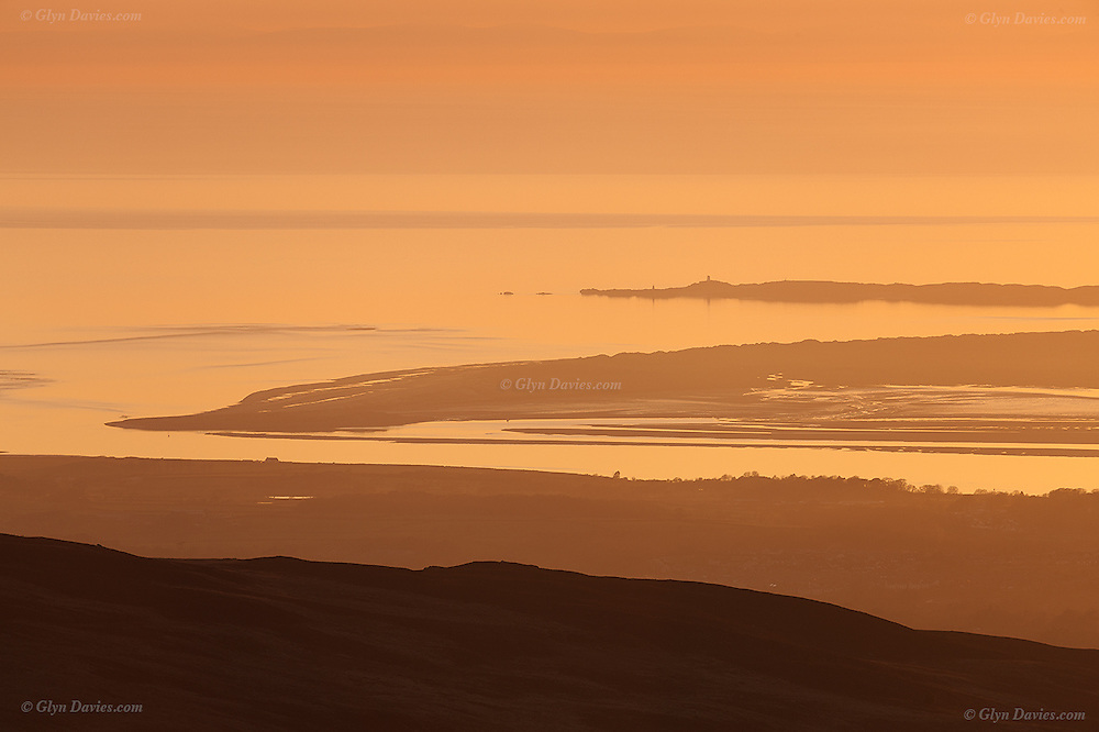 Sunset over the narrow channel of the Menai Strait at Caernarfon Bar with Llanddwyn Beach on Anglesey beyond, taken from the slopes of Elidir Fach mountain in Snowdonia.