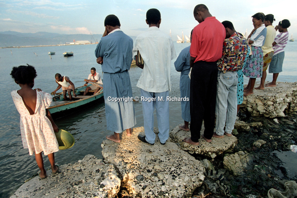 A group of worshipers pray before wading into a polluted bay for a baptism ceremony on a Sunday morning in Port-au-Prince, Haiti, May 1995. (Phoot by Roger M. Richards)