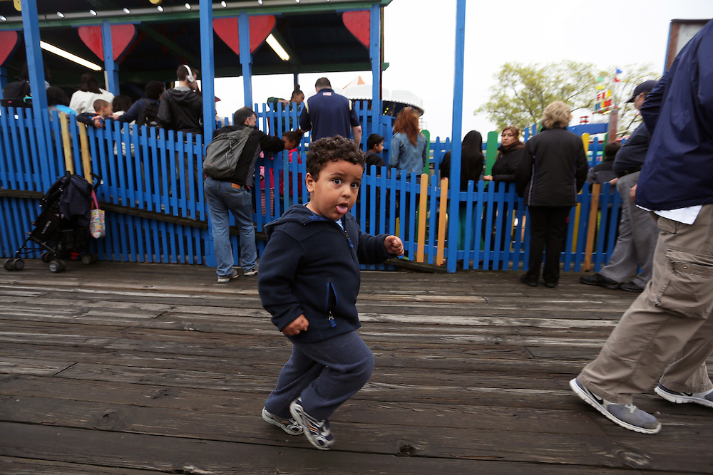 Xavier Mascareñas/Newsday; Alex Saroken, 2, of Manhattan, follows his father, Brian, to the next ride during Rye Playland's opening day festivities on May 11, 2013.