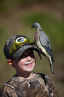 BOY WITH A DOVE DECOY ON HIS CAP