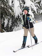 a woman cross country skis on a groomed ski trail on the Mount Tahoma Trails hut to hut ski trail system near Mount Rainier in the Cascade Range, Ashford, WA, USA