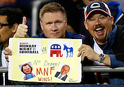 A pair of Chicago Bears fans hold up a sign showing their preference for Monday Night Football rather than the Republican and Democrat debate during the NFL week 7 football game against the Detroit Lions on Monday, Oct. 22, 2012 in Chicago. The Bears won the game 13-7. ©Paul Anthony Spinelli