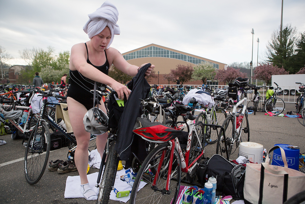 A participant in the O'Bleness Health System Race For A Reaon towel dries her hair as she transitions from the swimming to the cycling portion of the triathlon on April 26, 2014. Photo by Lauren Pond