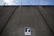 Frankfurt am Main | 01 Apr 2015<br /> <br /> Aussenmauer der Haftanstalt Frankfurt-Preungesheim mit einem Schild mit der Aufschrift &quot;Geb&auml;ude wird video&uuml;berwacht&quot;.<br /> <br /> &copy;peter-juelich.com<br /> <br /> [No Model Release | No Property Release]