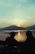 Silhouetted couple watch a romantic sunset, Sea Side, Highlands, U.K, 1999.