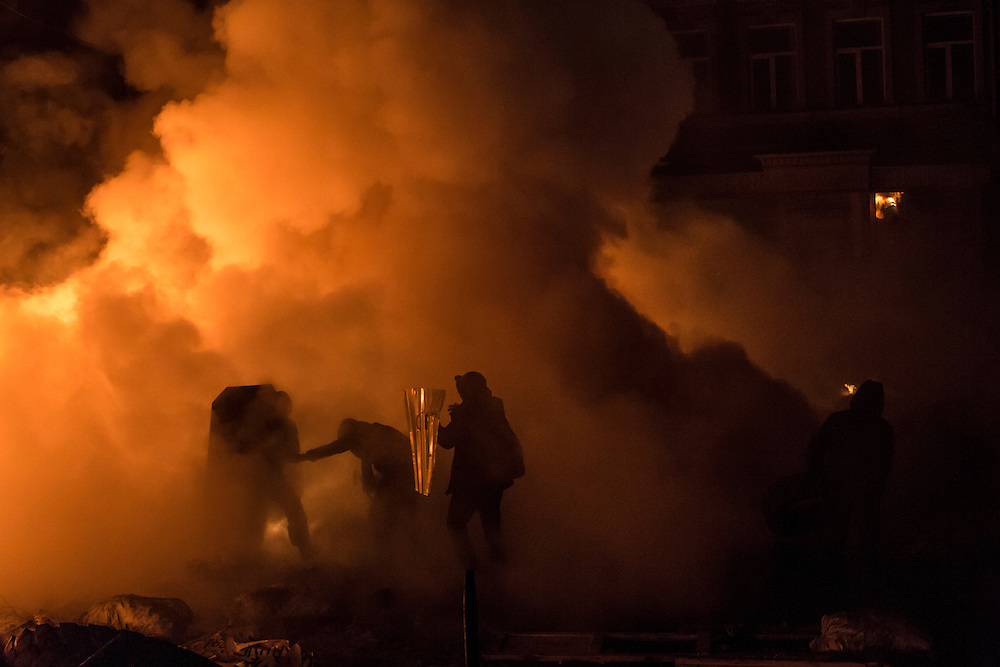 KIEV, UKRAINE - JANUARY 24: Anti-government protesters are engulfed by smoke from burning tires during clashes with police on Hrushevskoho Street near Dynamo stadium on January 24, 2014 in Kiev, Ukraine. After two months of primarily peaceful anti-government protests in the city center, new laws meant to end the protest movement have sparked violent clashes in recent days. (Photo by Brendan Hoffman/Getty Images) *** Local Caption ***