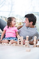 Cute girl teasing father while playing with wooden building blocks at home