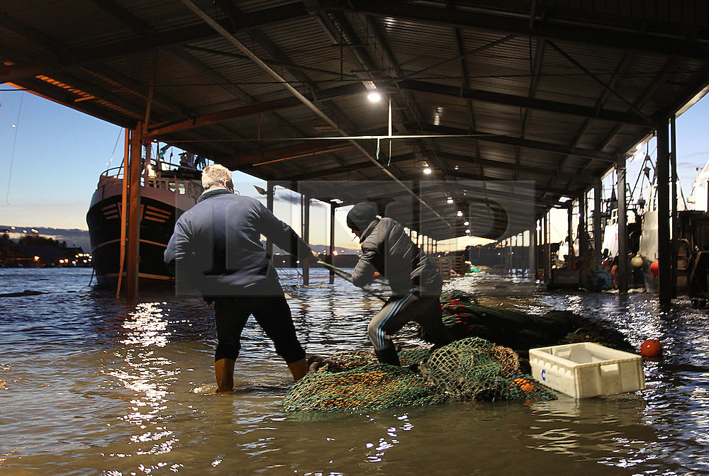 Licensed to London News Pictures. 05/12/2013. North Shields, UK, A high tide of over 6.6m - over 1m higher than predicted - floods the Fish Quay at North Shields.  Fishermen drag fishing gear to safety as the sea threatens to wash it into the river Tyne. Photo credit: Adrian Don/LNP
