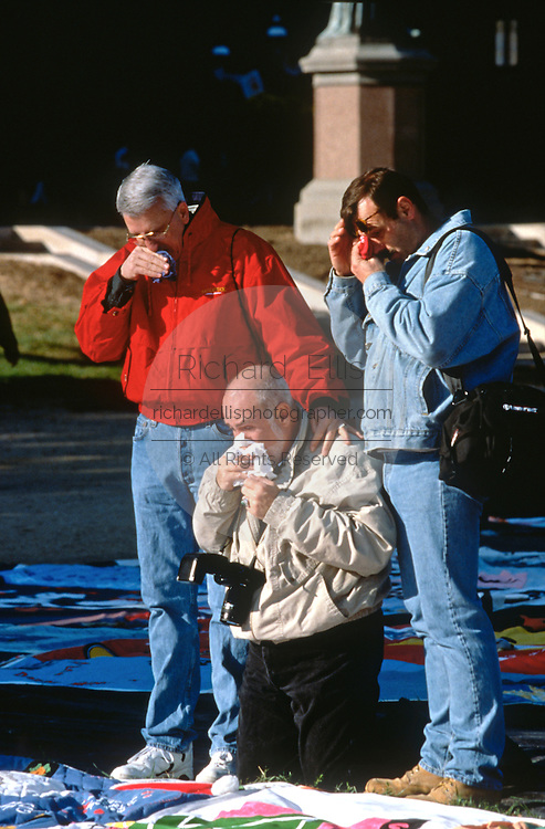 Friends comfort each other as they view the AIDS Memorial Quilt which was spread out along the National Mall October 12, 1996 in Washington, DC.
