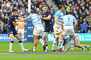 Sean maitland and James Ritchie are held back by Agustin Creevy during the Autumn Test match between Scotland and Argentina at Murrayfield, Edinburgh, Scotland on 24 November 2018.