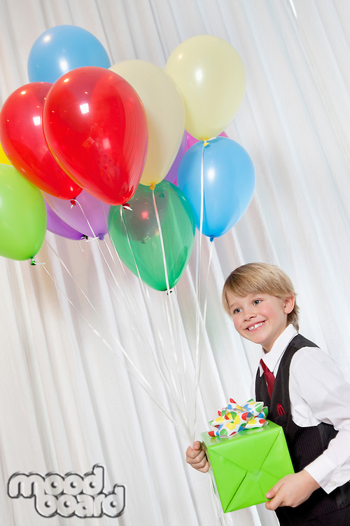 Happy young birthday boy with party balloon and gift looking away