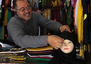 Iran, Fars Province, Shiraz, man putting a veil on a mannequin in the bazaar.